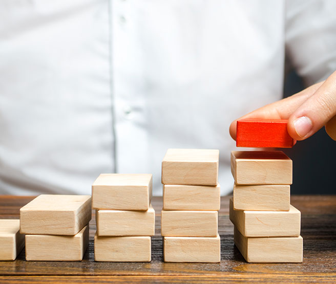 Man building a ladder or growth chart from wooden blocks
