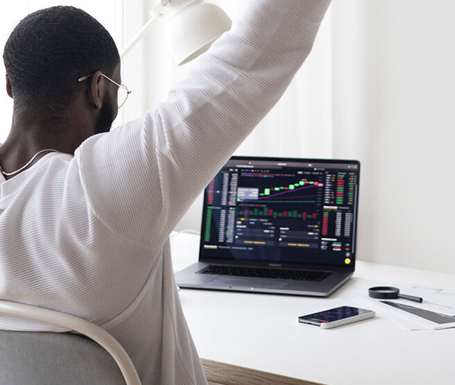 Happy broker looking at laptop screen showing stocks
