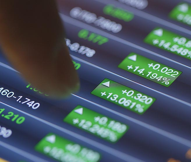 Man pointing at investment numbers on screen