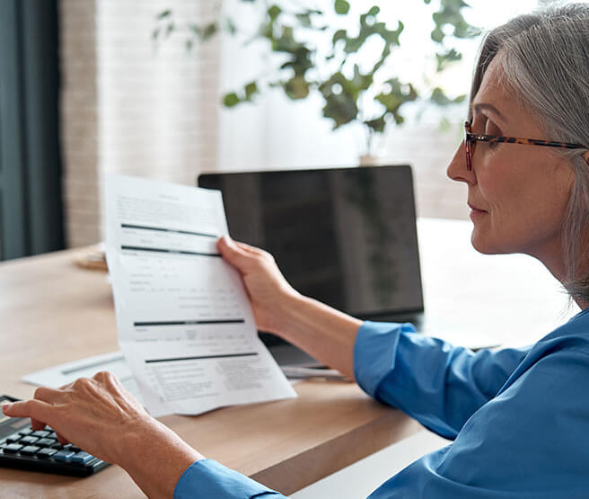 Mature woman with calculator and bill in right hand