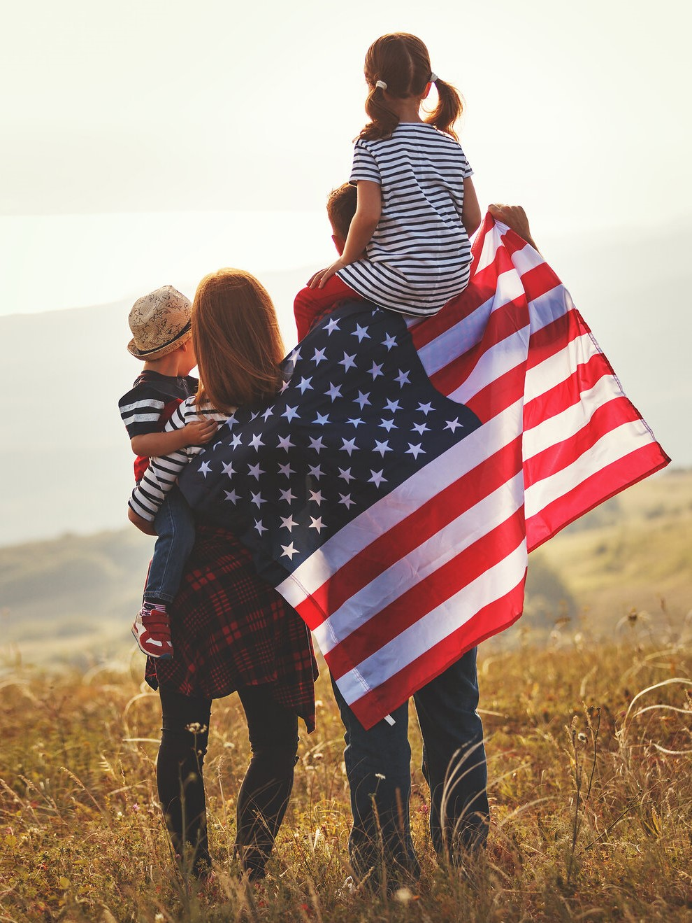 Happy family, parents and children with American flag outdoors
