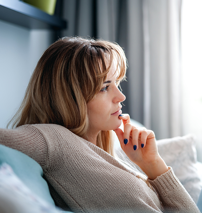 Woman thinking while sitting on the couch